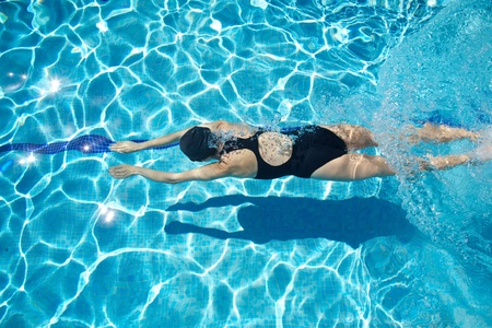 woman diving: woman with swimsuit swimming on a blue water pool