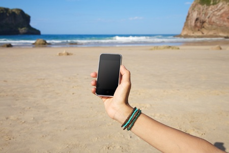 smart phone in woman hand on a beach in Asturias Spain photo