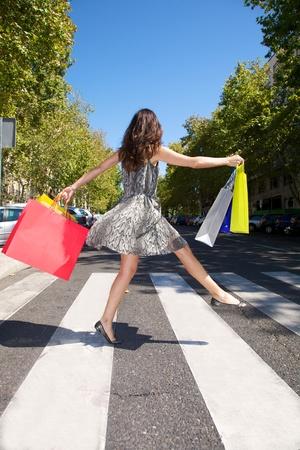 paso de cebra: mujer morena con bolsas de compras caminando en la ciudad de Madrid España