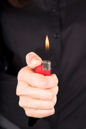 woman detail holding a red lighter in her hand photo