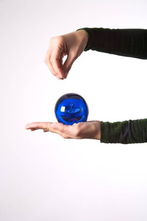 woman hand detail with a blue ball on her palm photo
