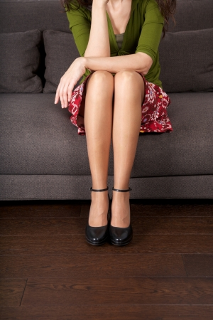 legs crossed at knee: woman detail sitting on a brown sofa