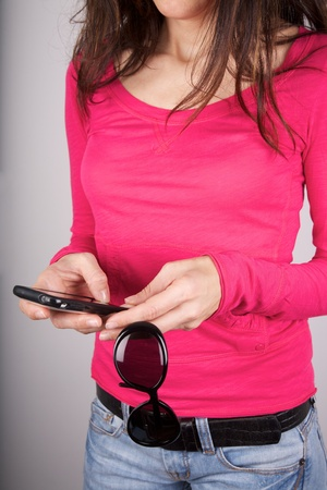 woman pink shirt detail holding sunglasses and smartphone Stock Photo - 12894208