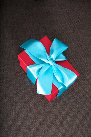 gift box red and blue on brown sofa seat  photo