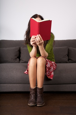 student reading: woman detail sitting on a brown sofa reading a book Stock Photo