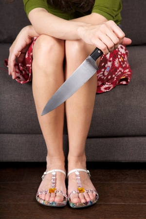 murdering: woman detail sitting on a brown sofa with a big knife