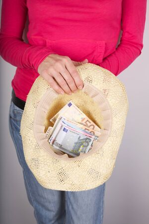 woman detail with group of Euro bills in her straw hat photo