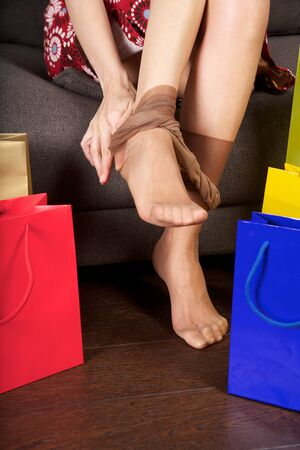 undress: woman detail sitting on a brown sofa between shopping bags