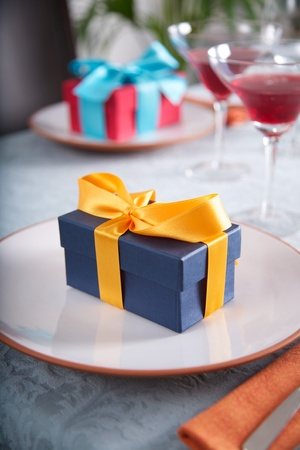 couple of gift boxes on white plates at restaurant photo