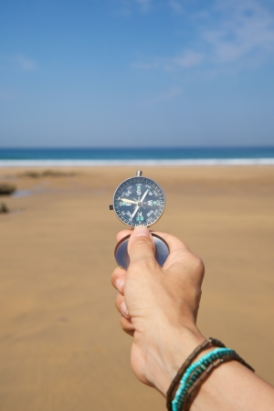 dial compass: woman hand with a black and silver compass in a beach