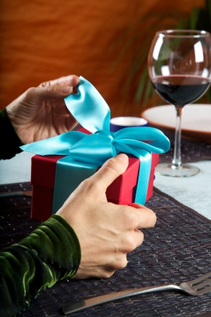 woman at restaurant opening a blue bow gift package photo