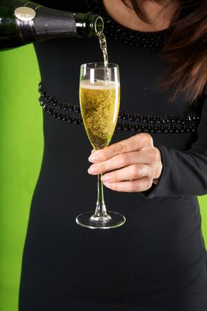 detail of woman hand with champagne glass on green background photo