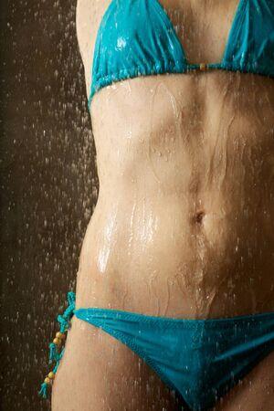 wet breast: woman taking a shower under water jet