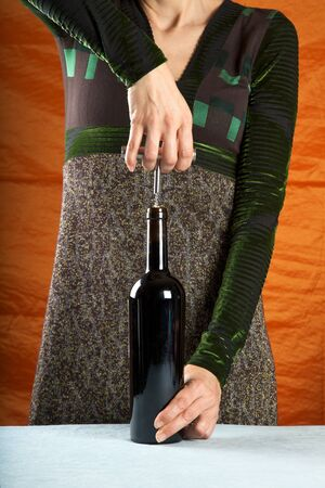 woman opening a red wine bottle with corkscrew photo