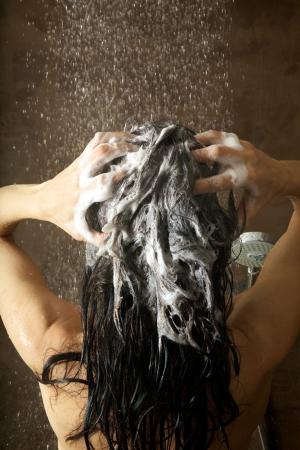 샴푸: 샤워 물에서 그녀의 머리를 세척하는 여자 스톡 사진