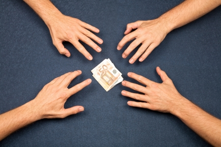 hand of four men and wad of euros on blue background photo