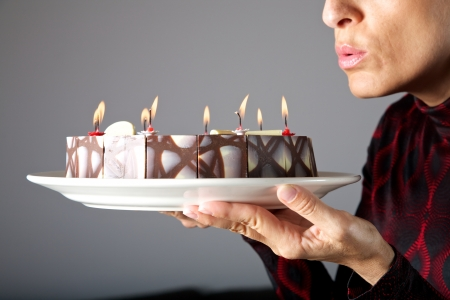 blowing out: adult woman hands holding a chocolate cake