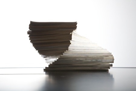 broadsheet: group of magazines piled on table and white background