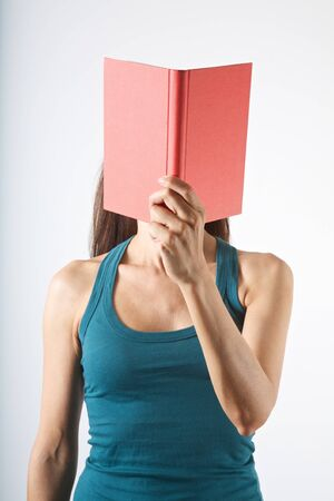woman with a book in her face on white background