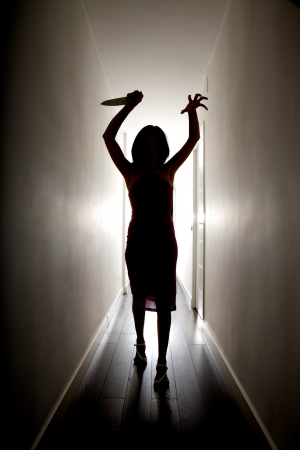 dark silhouette of woman with a big knife on her hand photo