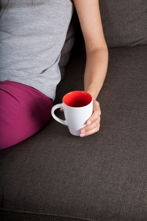 woman lying on brown sofa with tea cup on her hand photo