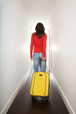 woman holding a suitcase in white passage indoor Stock Photo - 15177482