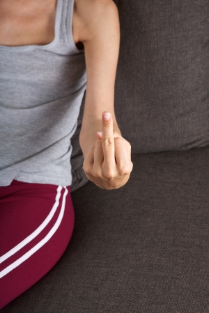 woman lying on brown sofa with third finger gesture Stock Photo - 15177487