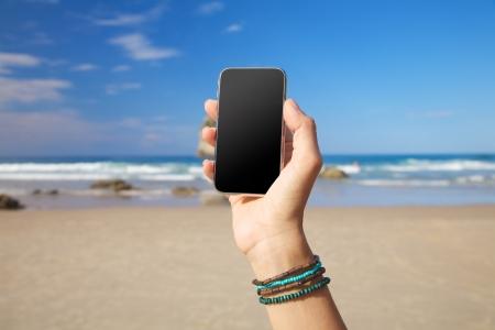 fiestas electronicas: tel�fono inteligente en mano de la mujer en una playa de Asturias Espa�a