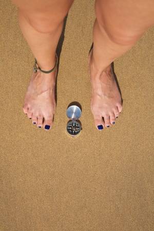 woman feet with a black and silver compass in a beach Stock Photo - 15755760