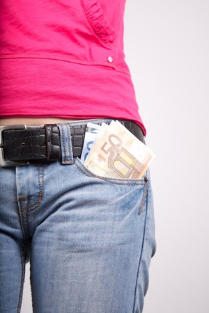 woman pink shirt detail with money in her pocket jeans photo