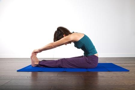 flexion: woman doing gymnastics on mat over white background