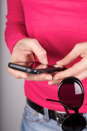 woman pink shirt detail holding sunglasses and smartphone photo