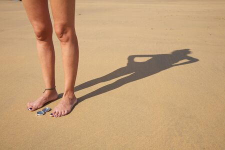 woman legs and shade with compass in a beach photo