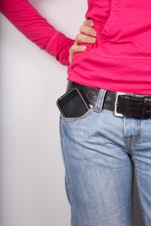 black belt: woman pink shirt detail with smartphone in her pocket jeans