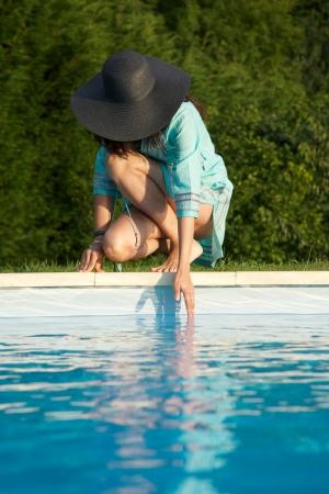 cuclillas: mujer descalza en la frontera de la piscina en Asturias Espa�a