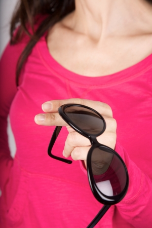 woman pink shirt detail holding a black sunglasses photo