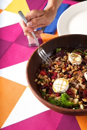 big salad in wood bowl on colorful tablecloth photo
