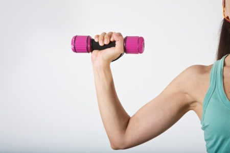 woman arm at gym lifting dumbbells over white background photo