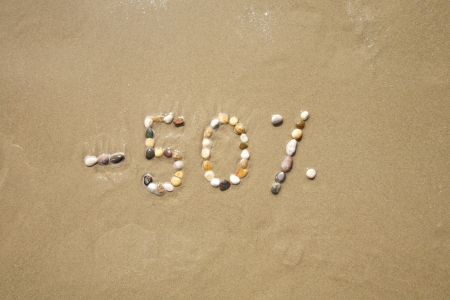 fifty percent discount word writing with small stones on sand beach ground photo