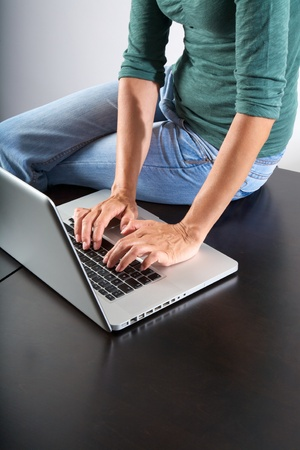 woman sitting on brown table typing on laptop photo