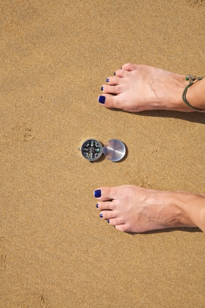 woman feet with a black and silver compass in a beach photo