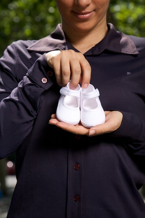 close up of white bootees in woman hand on dark blue shirt  photo