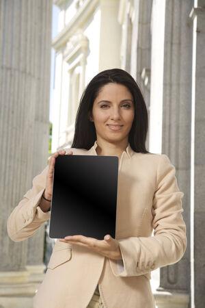 portrait of pretty businesswoman showing screen tablet  photo