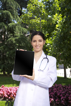 doctor young woman showing tablet over a green trees background photo