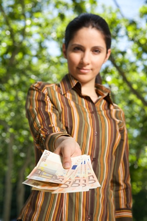 businesswoman offering you a banknote Euros in her hand  photo