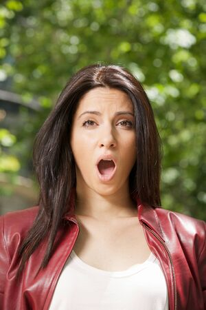 pretty woman open mouth face with red leather jacket Stock Photo