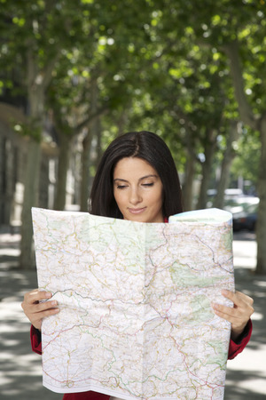 pretty brunette woman watching a map at street in Madrid city Spain photo