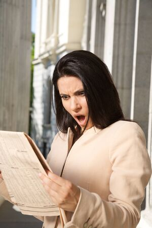 portrait of shocked woman reading financial newspaper  photo
