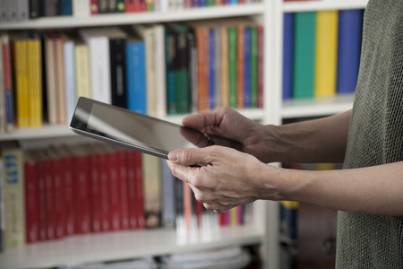 blank screen tablet in woman hands at library photo