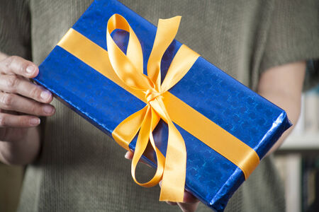 gift box in woman hands over library background photo